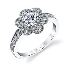 Flower Design Engagement Ring-This unique flower inspired #engagement #ring is gracefully accented by placing the 1 carat round brilliant diamond center in a halo of dazzling diamonds.The total carat weight of this delightful ring is 0.59. https://www.sylviecollection.com/flower-design-engagement-ring-sylvie-s1192