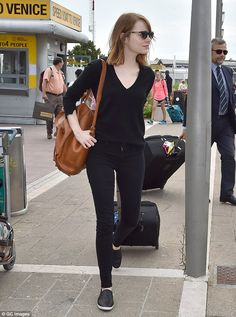 Low-key traveller: The Easy A star also chose a black knit and matching plimsolls, while carrying a large tan backpack