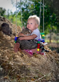 baby on swing with kitty