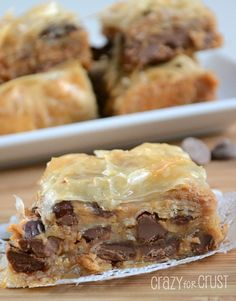 "Peanut Butter Baklava - Crazy for Crust | Crazy for Crust 1/2 pack Phyllo Dough (1 roll from a 2 roll box), defrosted 1 stick butter, melted 1 cup peanut butter About 2/3 of a bag of chocolate chips 3/4 cup chopped nuts (optional) 1 cup sugar 1 cup water 1/2 cup honey 1 teaspoon vanilla 9x9"" pan"