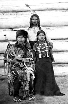 Crow native American, Son of the Star with an unidentified man and child. Son of the Star, is seated wearing a fur hat. Photographed by D. F. Barry. Date 188-?