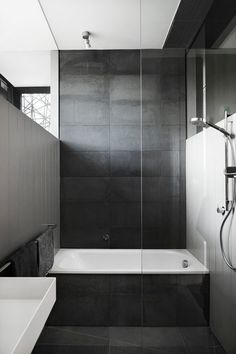 Bathroom Tile Idea - Use Large Tiles On The Floor And Walls (18 Pictures) | Large dark tiles cover the floor, bath surround, and back wall of this bathroom, creating a dark dramatic look, but when paired with white walls it creates a sophisticated look.