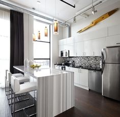 The gray and white striated marble island in this kitchen is absolutely stunning. Since the designer used a restrained color palette and didn't overdecorate, the rich materials are able to get all of the attention in this cool, modern loft kitchen.