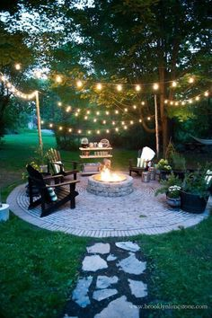 Twinkling Lights: A canopy of string lights defines this gorgeous patio with built-in fire pit. The lights also create a focal point that enhance the cozy vibe long after the last leaf has fallen from the tree. Click through for more beautiful fire pit ideas. #pergolafirepitideas