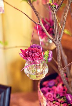 """Small glass vases of flowers hung from the branches of a """"wishing tree"""" under which guests could leave notes for the couple. Photo: Katie Stoops."""