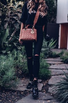 An all black outfit with a caramel brown Dior studded Miss Dior bag - love using accessories for a touch of color in an outfit - wearing black skinny ripped jeans, black cropped sweatshirt, and black Balenciaga cutout boots #casualoutfit #casualfashion #outfit #allblack #DiorBag #studdedbag #skinnyjeans #BalenciagaBoots #croppedsweatshirt