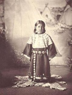"""DUNN GIRL— Dentialia cape with a glass trade bead necklace over a trade cloth dress trimmed with """"hawk"""" bells, flat trade buttons, dentalia and what appears to be imitation elk teeth.  The belt or """"drag"""" is of trade silver conchos. She is standing on a bobcat skin.  ca. 1900's. 6 ¼ x 8 ¼ inch mounted on 11x14 inch archive rag board."""
