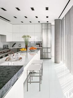 The kitchen is outfitted with Poliform cabinetry and stools, a Sub-Zero refrigerator, and white crystallized-glass countertops by Architectural Systems | archdigest.com
