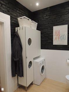 Do ustawienia pralki wykorzystano tu oryginalną szafkę, nawiązującą kształtem do pralki. Z boku zawieszono praktyczne wieszaki, a na górze ustawiono białe kosze ładnie kontrastujące z czarną ceglaną ścianą.