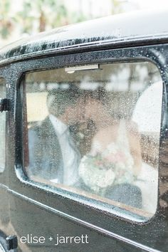 sometimes rain on your wedding day is awesome. love this portrait of bride and groom cozy in an antique car