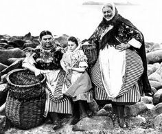 Fishwives of East Neuk, Fife, in their traditional dress and folded aprons.  Notice the size of the large keel that would be filled with fish and carried long distances on their backs to the fish market.