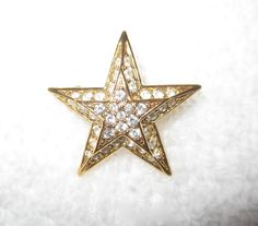 """One of almost 40 pins we bought at the Joan Rivers' estate auction--these were her favorite pins that she actually wore, from her personal jewelry box! A wonderful gift or treat yourself to a piece of history from a true queen of comedy and wonderful designer. The petite star. Gold tone and encrusted with white crystals. Pictures shown with and without flash. Approximate measurements: 1 1/8"""" diameter.  Condition: superb!"""