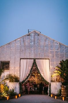 Greenhouse wedding reception with romantic lighting. Floral design with eucalyptus garlands and protea. Antique vineyard chairs at long feasting, farm tables. Gold flatware, boho chic decor and table settings. This bea