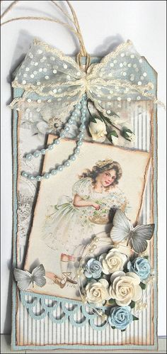Handmade tag in muted blues and ivory, with vintage image of little girl, flower and butterfly embellishments, and sheer ribbon bow