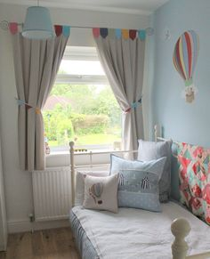 Day bed with cushions... bunting curtains and hot air balloon stickers from Belle & Boo