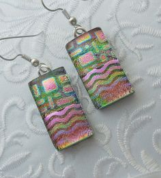 Multiple layers of dichroic glass are fused together to make these beautiful glass earrings. Main colors are multi colored rainbow dichroic layered on black glass. Capped with clear glass for depth and brilliant intensity. About 1/2W x 1L. Sterling silver ear wires. Here are some of my other glass earrings >>> https://www.etsy.com/shop/GalaxyGlassStudio?section_id=5903483&ref=shopsection_leftnav_1  Enter my shop here: galaxyglassstudio.etsy.com Sign up for my newsletter for special coupons…