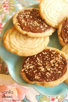 Vanilla Crisps - Crisp vanilla flavored cookies topped with melted chocolate and nuts. They look delicious!