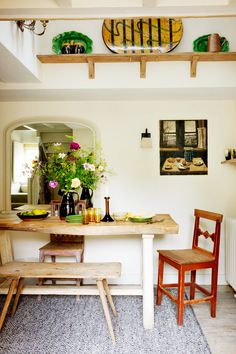 Rustic and charming dining space with flowers on table and high shelf for displaying decorative platters