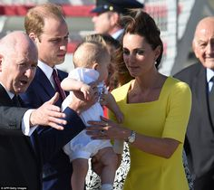 Careful: William passes baby George back to his mother as her glossy hair is blown back in the wind