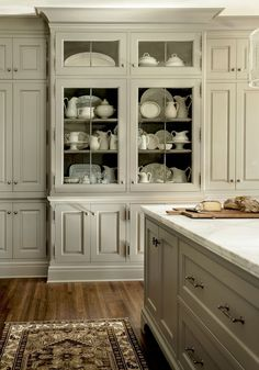 built in kitchen cabinets in a sage-y khaki color - Maybe Nantucket Gray? with glass front, cabinet color, white marble