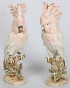 Czechoslovakia ~ A pair of Royal Dux ~ porcelain Cockatoo figures ~ Matching cockatoo figures are perched on a branch with leaves below ~ They have a white feathered body with pink highlights ~ Circa 1901-1950