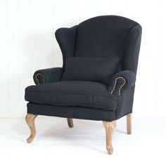 Black French Linen Wingback Chair - Handcrafted from solid birch and upholstered in 100% black linen, the new wingback armchair is a welcome addition to our chair family.  Attractive brass trims finish the rolled arms, one rectangular matching cushion is included.  The matching black linen ottoman looks fabulous with it.
