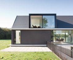 Slate roof. Protruding floor plinths. Stylish bricks. Glass Dormer