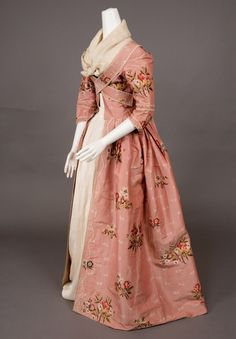 Robe à la Francaise, 1770-1780. Rose pink ribbed silk brocaded with scattered multicolored flower sprays and small cream flower sprigs, looped cream silk fringe trim, bodice with pendant self fabric bands to cross-over and pin under arms; linen lining.