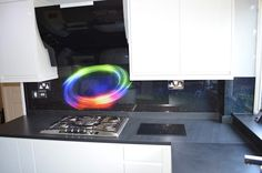 """Rainbow Ring in Rainbow Glitter Dust"". Bespoke glass kitchen splashback by Creoglass (London, UK). View more kitchen splashback ideas on www.creoglass.co.uk"