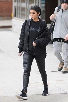 Kylie Jenner wearing J Brand L8007 Edita Leggings in Black, Adidas Tubular Defiant Sneakers in Core Black/Core White, Vetements Sweatshirt and Nomia Oversized Bomber Jacket in Black