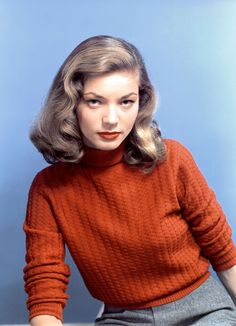 Lauren Bacall in an orange turtleneck and matching orange lip with grey tailored trousers.