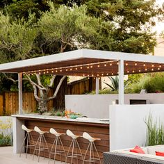 """Outdoor bar:  Elaine Barden envisioned her backyard retreat as """"Palm Springs meets W Hotel style."""" Her designers chose a custom fabricated aluminum arbor above an outdoor bar. The team built it on-site and painted it silver to match the wall sconces. Redwood slats cover the top."""