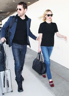 Kate Bosworth wears a black top with jeans and red Prada patent leather loafers.