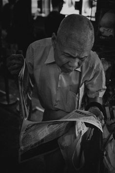 I just stand under the shelter, was raining at that time, while standing i saw an old man trying to read the newspaper while he was standing as well, so i approached him slowly and just about in front of him, i taken this picture.