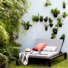 idées déco terrasse avec un jardin vertical en pots de plantes vertes, aménagée avec un bain de soleil moderne