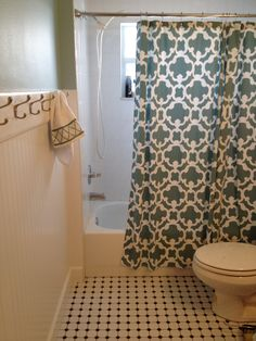 We added beadboard to the walls topped with a 1x6 and some moulding to hold enough towel hooks for three kids and their wet bathing suits! The trellis shower curtain and matching towels were a deal at Target. The biggest difference was adding the vintage style porcelain tile to the floor in the bathroom and the alcove.