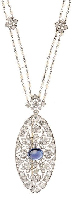 An Edwardian diamond and sapphire pendant/brooch. The pendant centring a cabochon sapphire suspended from a seed pearl and diamond cluster double chain with a marquise diamond clasp.
