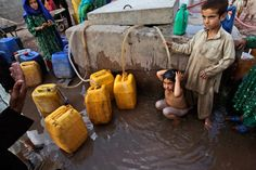 Daily Life: May 2012 - A man asks an Afghan refugee not to bathe at a water point, while others collect water, in a slum area on the outskirts of Islamabad, Pakistan, May 15, 2012. People in Pakistan are facing water shortages due to low water levels in the country's dams, according to the Pakistani Meteorological Department.(Muhammed Muheisen/Associated Press) #