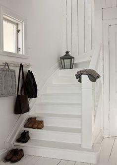 Puuportaikosta poistettiin remontissa muovimatto. Portaikko hiottiin ja maalattiin valkoiseksi. Päätyseinä on alkuperäistä lautaa. Vasemmalla oleva naulakko on hankittu Tanskasta. Lasten kengät säilyvät hyvin portaissa.