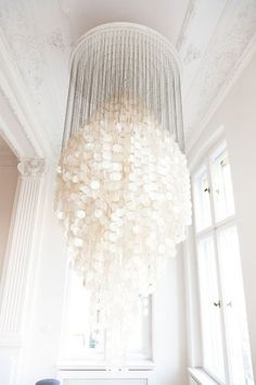 Amazing large capiz shell chandelier in traditional white space. Capiz Chandelier, White Chandelier, Modern Chandelier, Seashell Chandelier, Chandelier Crystals, Crystal Chandeliers, Chandelier Lighting, Luminaire Design, Shades Of White