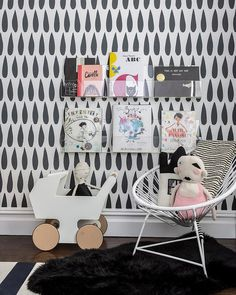 Black and white kid's room features an accent wall clad with Sissy + Marley Drops Charcoal Wallpaper lined stacked acrylic book ledges over a white reading chair atop a black sheepskin pelt.