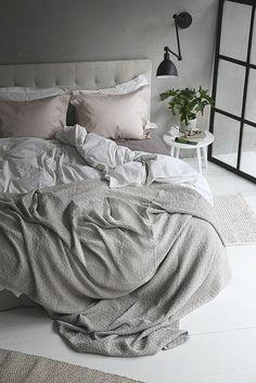 chambre à coucher gris avec ligne de lit gris , plantes vertes et murs gris