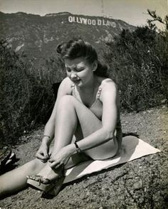 """Sunbathing…In the background the old """"Hollywoodland"""" sign missing the """"H"""" before being repaired and changed into """"Hollywood"""" in 1949."""