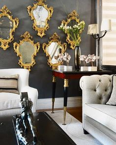 What a fabulous side table, love the grey walls and mirrors grouping, chesterfield sofa and that sculpture in the coffee table...