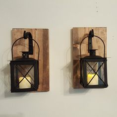 This is a beautiful rustic set of two black metal and glass lanterns each hanging from a wrought iron hook, the wood has been stained an early american color. Ready to hang securely to your wall with a sawtooth hanger on the back.  Overall Size: Wood base is 10 x 5 1/2 inches. Lantern is 4x4 inches square and 7 inches tall with the handle extended.  Each board may not look exactly as pictured due to the unique nature of the wood. Some may have knot holes and/or cracks which makes each board…