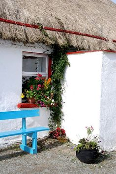 Cottage with bench, flowerers, and thatched roof in Donegal, Ireland