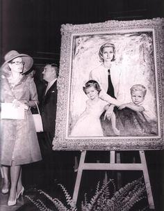 Princess Grace walking by a portrait of herself with Princess Caroline and Prince Albert