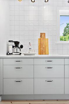 Kök med helt slät vit lucka och handtag i krom och läder| Ballingslöv