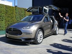 """Tesla unveiled the Model X, a sleek-looking cross between a minivan and SUV with clever """"falcon wing"""" doors and a new electric all-wheel drive system."""