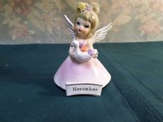 "For sale is a vintage November birthday angel made by Nanco of Boston, MA. The angel measure 4 1/4 "" high x 3"" long base, and is in fine used condition with no chips or cracks, has original silver foil stickers, scuff marks from sitting on shelf. The left wing is shorter than the right, but has glaze over the tip.  